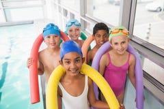 Poolside sonriente de la clase linda de la natación fotografía de archivo libre de regalías
