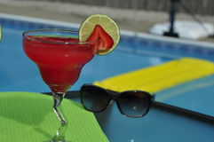 Poolside Strawberry Margarita on the Rocks with Sunglasses. Glass of Strawberry Margarita on the Rocks with Sunglasses by a Swimming Pool with Flotation Device stock images