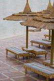 Poolside sunbeds mit Sonnenschirmen Stockfoto
