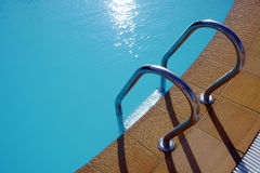 Poolside at a tropical hotel. Blue hotel and swimming pool Royalty Free Stock Photography
