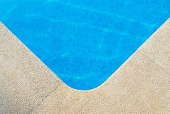 Poolside view. Close up of the corner of a swimming pool royalty free stock images