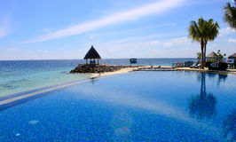 Poolside view of the beach. Indian ocean view from a infinity pool side royalty free stock photo