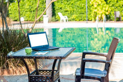 A poolside work desk with a table. Top, coffee mug and notebook is placed on a table with a blank screen Royalty Free Stock Photos