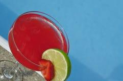 Poolsidejordgubbemargaritan på vaggar med limefruktgarnering Arkivfoto