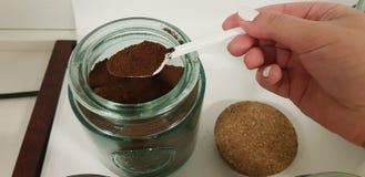 Poon con caffè nero preso da una persona dalla latta di vetro immagini stock libere da diritti