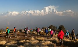 Poon hill with tourists and mount Dhaulagiri. POON HILL, NEPAL, 8th APRIL 2016 - morning view of Poon hill with tourists and panoramic view of mount Dhaulagiri stock photo