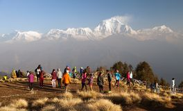 Poon hill with tourists and mount Dhaulagiri. POON HILL, NEPAL, 8th APRIL 2016 - morning view of Poon hill with tourists and panoramic view of mount Dhaulagiri stock photos