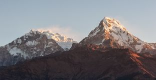 Poonhill view of Annapurnas. Warm pink and orange sunrise light over Annapurna mountain range with blue sky and beautiful clouds. View from Poon hill in stock photography
