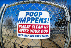 Poop Happens. A sign reminding to people clean up after their dogs Royalty Free Stock Image