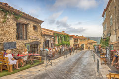 Poople não identificado que come no restaurante da rua, arquitetura da cidade de Ramatuelle em Riviera francês, França Imagens de Stock