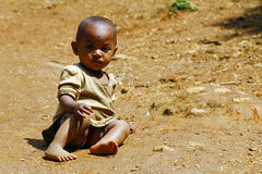 Poor african kid on ground, Madagascar Stock Photos