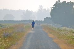 Poor Air Quality and Health. Poor air quality caused by nearby forest fires and drought doesn`t deter a jogger from pursuing his daily run near Chilliwack, BC royalty free stock photo