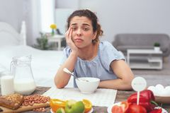 Adolescent lady suffering from low appetite. Poor appetite. Adolescent lady over a dinner table looking uninterested in her meal obviously experiencing terrible Stock Photography