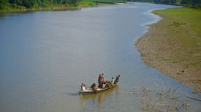 Fishermen are travelling on a boat in the river unique photo. Poor Bangladeshi fishermen are travelling with a boat in the river isolated unique editorial image royalty free stock photography