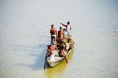 Fishermen are travelling on a boat in the river unique photo. Poor Bangladeshi fishermen are travelling with a boat in the river isolated unique editorial image royalty free stock photos