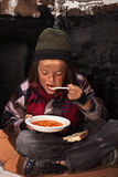 Poor beggar child eating charity food. On the street sitting on cardboard plank royalty free stock images