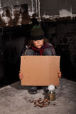 Poor beggar child on the street with blank sign royalty free stock photography