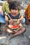 Poor Beggar Girl. A poor beggar girl from India eating a watermelon royalty free stock photos