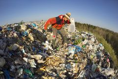 Man with a bag picks up trash stock photo