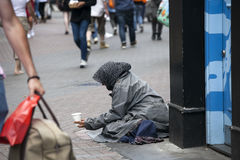 The poor beggar woman sits on the pavement. Royalty Free Stock Photos