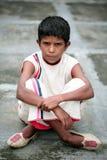 Poor boy. Poor indian boy sitting on road stock image