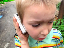 Poor boy. Poor kid from a poor family call on the mobile phone Royalty Free Stock Images