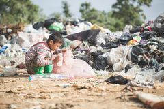 Poor boy collecting garbage in his sack to earn his livelihood, The concept of poor children and poverty stock photos