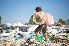 Poor boy collecting garbage in his sack to earn his livelihood, The concept of poor children and poverty royalty free stock image