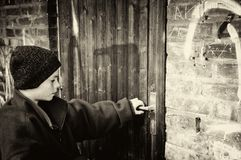 Poor boy  opens door of his home Stock Photo