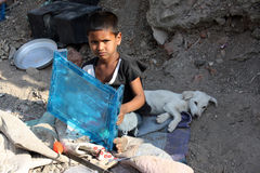 Poor Boy & Dog. A poor boy sitting on the street-side with his white pet dog in India Royalty Free Stock Photos