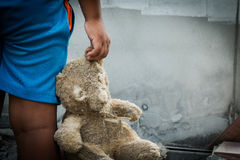 Poor boy holding a teddy bear Royalty Free Stock Image