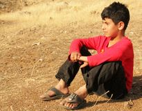 Poor boy. A poor boy sitting on the ground and waiting his father back to home. kurdistan, iraq royalty free stock photos
