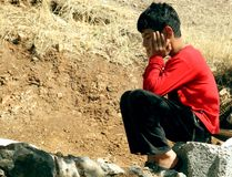 Poor boy. A poor boy sitting on the ground and waiting his father back to home. kurdistan, iraq stock images