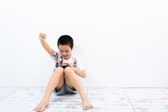 Poor boy and smartphone. Younger Asian poor boy got a new smartphone and looks happy. Social network concept royalty free stock photo