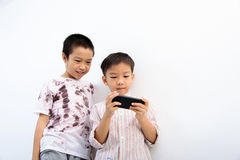 Poor boy and smartphone. Younger Asian boy play smartphone, another poor boy looks interest at phone at the white wall. Social network concept royalty free stock photos