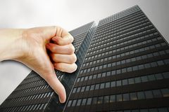 Poor Business. A thumbs down sign with a tall building in the background Stock Photography