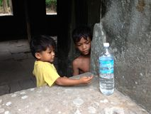 Poor Cambodian Children. SIEM REAP,CAMBODIA-April 10:The clean water is limited in Cambodia.These poor children  only had one bottle of water for a whole day in Royalty Free Stock Image