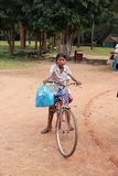 Poor cambodian kid playing with bicycle stock photos