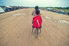 Poor cambodian kids racing with old bicycle. Tonle Sap lake. Cambodia Stock Photo