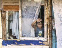 Poor child in a decaying house. A child looking through the window, in a poor Romanian village Royalty Free Stock Photography