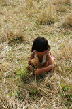 Poor child on dry grass meadow. VIET NAM, BUON ME THUOT-  DEC 31, 2012: Two Asian children with pretty face looking vegetable on dry grass meadow, poor child at Stock Photo