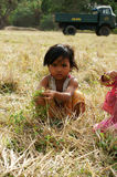 Poor child on dry grass meadow. VIET NAM, BUON ME THUOT-  DEC 31, 2012: Two Asian children with pretty face looking vegetable on dry grass meadow, poor child at Stock Photos