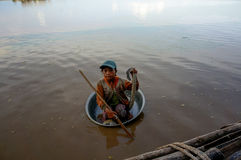 The poor child floats in a basin of dirty Tonle SAP lake Stock Image