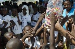 Poor children getting candies Stock Photo