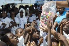 Poor children getting candies Stock Images