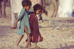 Poor children from India. Two poor and dirty children from the Indian city of Pushkaror Pushkar Mela play on the dusty street.Pushkar Mela, is a colorful and Stock Photography