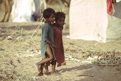 Poor children from India. Two poor and dirty children from the Indian city of Pushkaror Pushkar Mela play on the dusty street.Pushkar Mela, is a colorful and Royalty Free Stock Photography