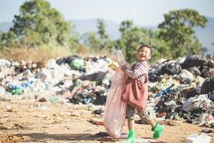 Poor children smiling happily while walking garbage collection for sale,  the concept of poor children and poverty stock photo
