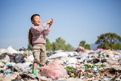 Poor children smiling happily while walking garbage collection for sale,  the concept of poor children and poverty royalty free stock image