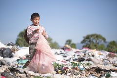 Poor children smiling happily while walking garbage collection for sale,  the concept of poor children and poverty stock photography